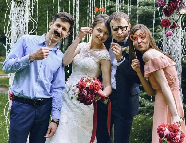 happy guests and bride and groom having funny photos